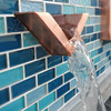 Bobe Water And Fire: Picture of Wedge Scupper shown with the smooth copper finish and bubbling water falling down into the pool below.