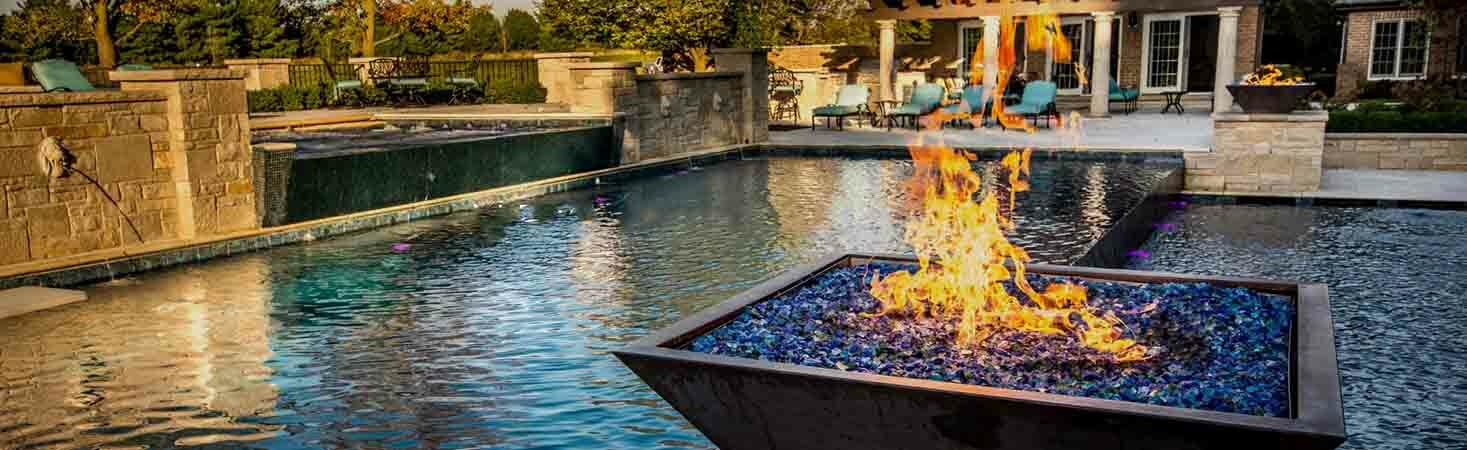 Outdoor water and fire feature copper fire pit bowl next to pool