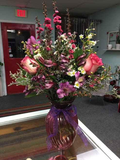 These flowers will have her feeling like she is walking in a meadow surrounded by flowers.  Seasonal wildflowers in purples and pinks and tied with a bow make up this lovely arrangement.