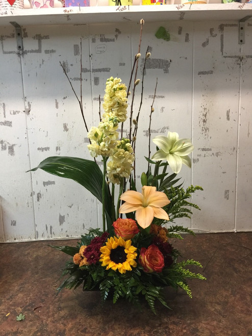 Let us wow you with this artistic arrangement including sweetly scented stock, curly willow, lilies, roses and sunflowers.