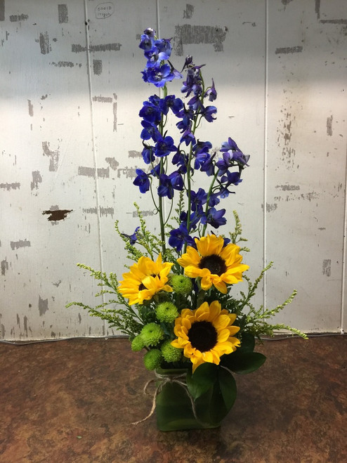 Make a statement with this impressive grouping of blue delphinium and sunflowers, accented with a splash of green and a touch of yellow.