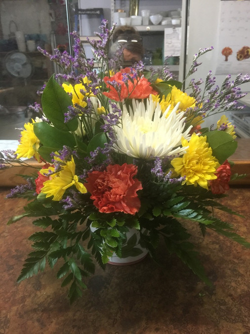 Brighten her day with this pop of orange, yellow and white carnations, mums and daisies nestled in a bed of greens and limonium.