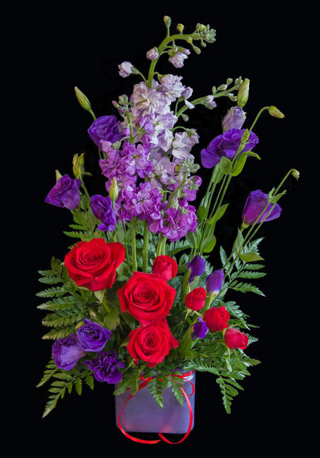 She will feel like royalty when she receives this intoxicating mixture of sweet smelling stock, double purple lisianthus, purple iris and red roses.  not just your ordinary floral arrangement.