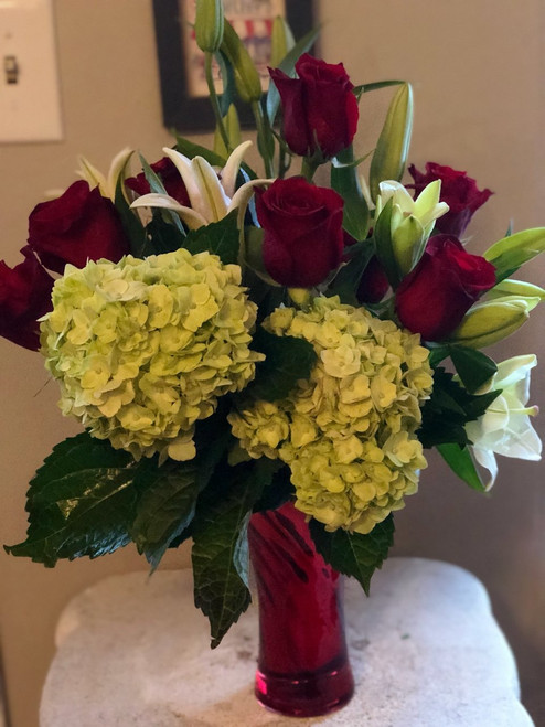 If she knows her flowers, she will love this arrangement:  hydrangeas,red roses, and oriental lilies gathered together in a red vase