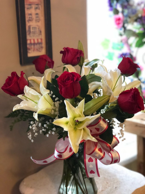 Passionate Red roses mixed with Lilies and Babies Breath  and arranged just for you with a red and white bow