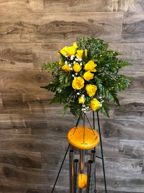 An unusual and memorable way to send your condolences - Footprints in The Sand Wind Chimes displayed with fresh yellow roses and greens on a standing easel.