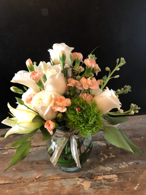 Oodles of Blush Roses, White lilies, peach mini carnations, stock and green dianthus nestled together with seeded eucalyptus in a fluted rose bowl lined with lily grass and a delicate bow will make her swoon.