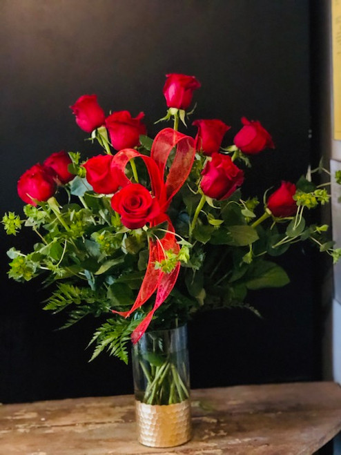 She won't be able to resist one dozen of our premium 60 cm red roses arranged in a cut glass vase with hammered gold at the base.