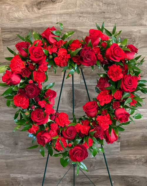 "Express your heartfelt sentiments  with this large heart full of fresh roses and carnations displayed on easel.  Shown in classic red on 18"" form - actual width 24"".  Can be done in your choice of color and sized up to 22"" form with choice of luxury."