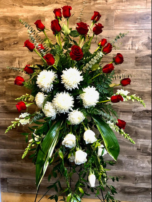 A royal way to show your love and respect, this standing spray contains 2 dozen red roses, 1/2 dozen white roses and 7 football mums all arranged amid Italian ruscus, varigated aspidistra and eucalyptus.