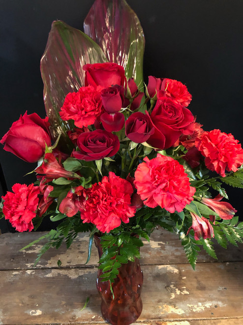 Show your romantic side with Red - the color of love -  in Roses,  carnations, peruvian lilies, even red ti leaves arranged with greens in a red vase.