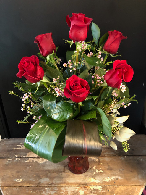 When you want to give a dozen red roses, but your budget says not, we have the solution, 6 luscious red roses all dolled up with ti leaves, salal, eucalyptus and limonium in a red vase.