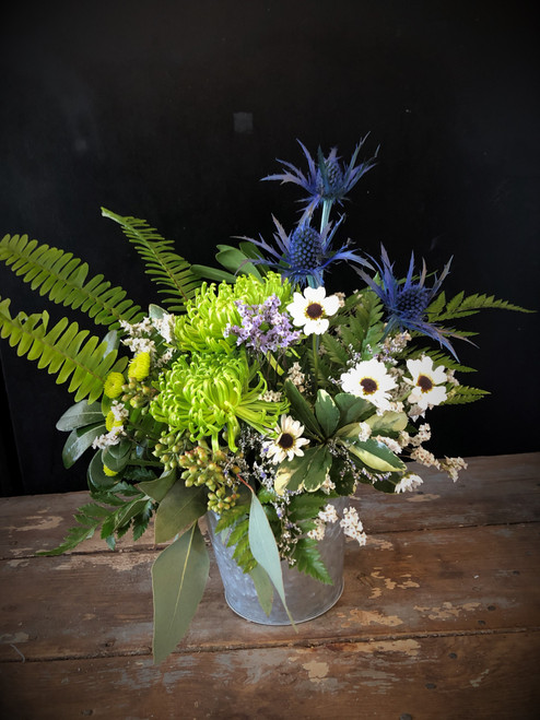 The spirit of calm, clean air and peace abound in this peaceful modern arrangement of green spiders, blue thistle and ying yang daisies, a unique and modern arrangement that will work for nearly any occasion.