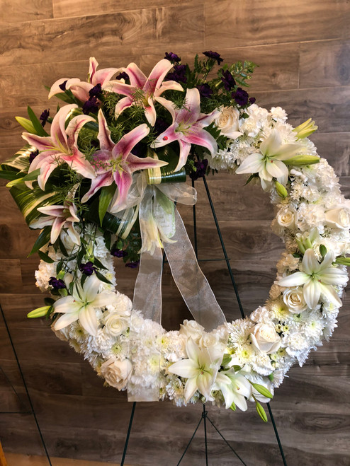 One of our favorites, this amazing expression of love is sure to impress.  Stargazer lilies nestled above a solid wreath of carnations, mums, roses and lilies in white, displayed on an easel for eye level viewing.