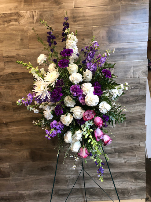 A peaceful expression of love and passage with roses, stock, lark, mums and carnations in varying shades of purple, lavender and white, displayed on a standing easel for all to see.