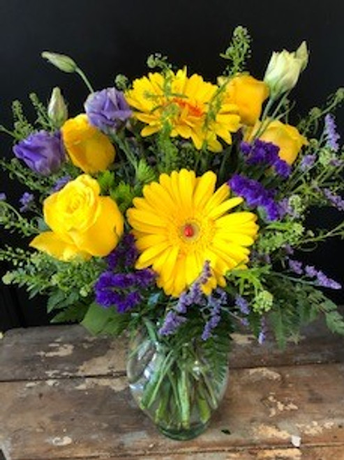 Sunny, Happy, Joyful - all the things you want to show and send - this vibrant bouquet in yellows and purples, featuring gerberas and roses will get you there.