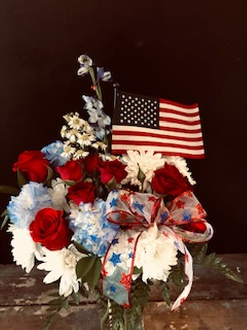 Perfect for your 4th of July Celebrations - this red, white and blue arrangement with roses, carns, delphinium, asters and mums is accented by a patriotic bow and an American Flag.  Special pricing for 4th of July!
