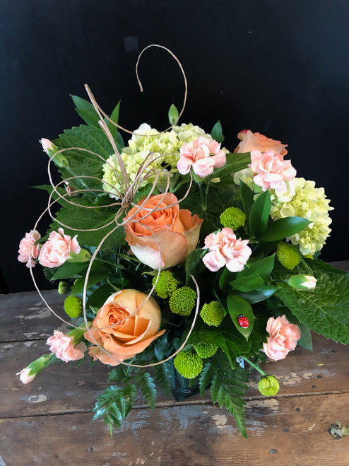Serene and lovely are these peach roses and green hydrangeas, accented with peach mini carns, green buttons and luscious greens.
