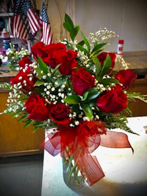 Regal Red Roses with a twist - non - traditional wave shape, accented with babies breath and Italian Ruscus and luscious red bow
