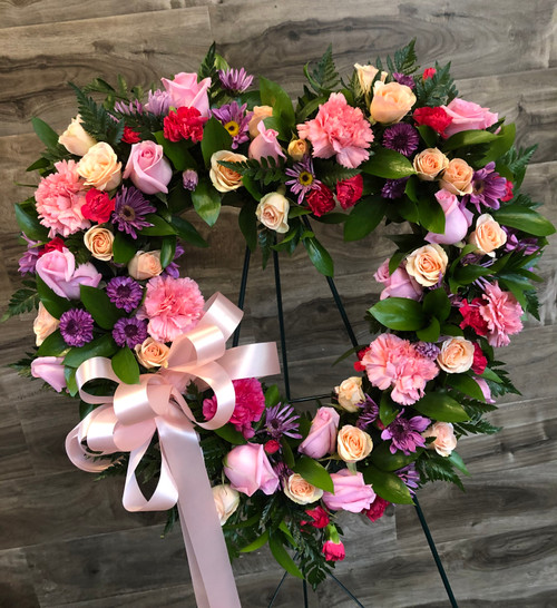 Send your sympathy with our precious hart easel is filled with roses, spray roses, carnations and daisies in shades of pink and lavender, accented with a big pink flowing bow.