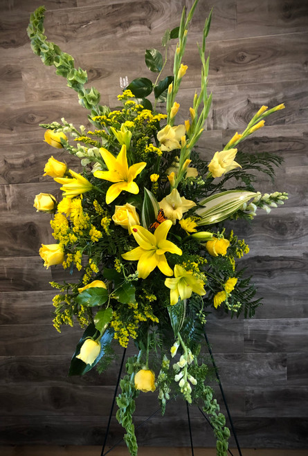 Nothing shows your sentiments of friendship better than this glowing display of yellows. Lilies, roses, glads,  and solidago are stars shining amid classic greens and belles of Ireland - all displayed regally on a standing easel.