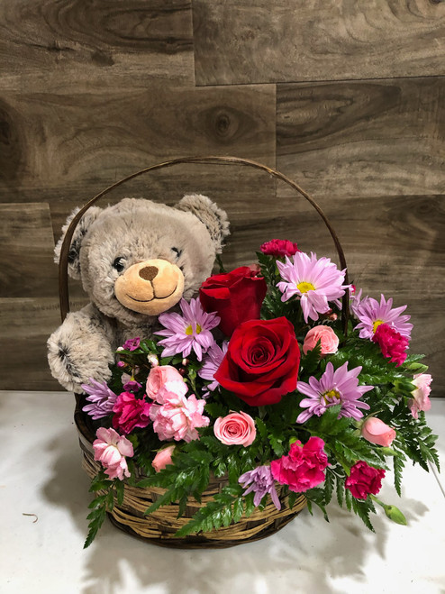 What better gift than a basket full of fresh flowers and a cuddly stuffed bear?