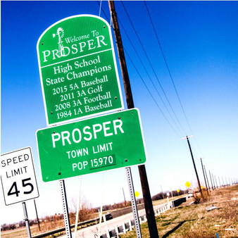 Welcoming visitors and locals to its affluent town is this Prosper city limits sign. Being that Prosper is a rather small town, residents' pride is even larger which is why the local high school's state champion titles are also featured here.
