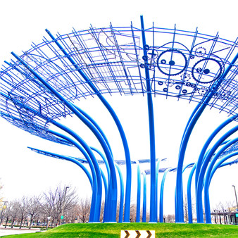 """The sculpture consists of 25 poles and five art panels. It weighs 410,000 pounds and required 650 gallons of custom """"Sharpie blue"""" paint to complete. The four-story-high sculpture was designed by landscape architect Michael Van Valkenburgh and artist Mel Chin with the aid of LeMessurier Consultants, and was fabricated and erected by Big D Metalworks of Dallas."""