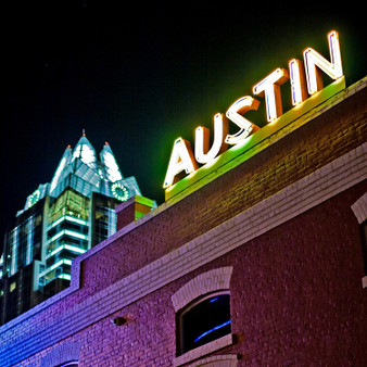 This neon sign sits atop an old red brick building in downtown Austin, Texas.