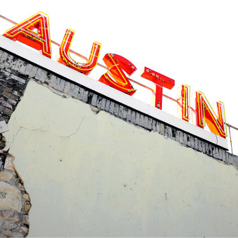 This red sign sits atop an old red brick building in downtown Austin, Texas.