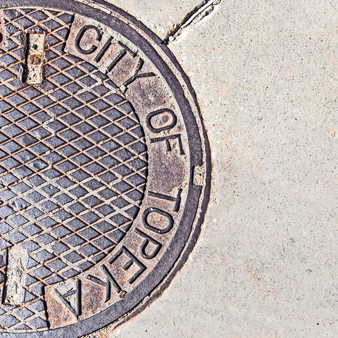 <p>This artistic photo puts a creative spin on a common object - a manhole cover in Topeka, KS.  <p><p>Click &lsquo;Choose a Product&rsquo; above to get this image hand printed on a ceramic 4x4 custom coaster, cutting board, magnet, ceramic trivet, ornament, dog tag or canvas.</p>