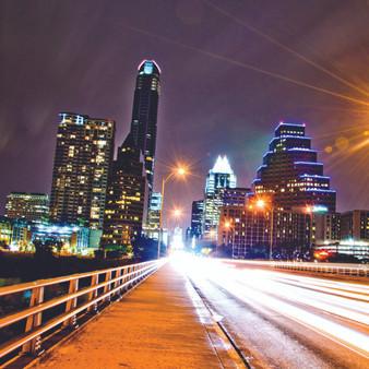 This photo was taken on Town Lake Bridge in Austin, Texas showing the skyline at night.