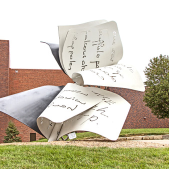 """""""Torn Notebook"""" is in three pieces — a primary notebook structure and two other pages that look to be blowing away in the wind. The primary structure is 22 feet tall and 35 feet long. The sculpture is made of stainless steel, steel, and aluminum, all painted with polyurethane enamel."""
