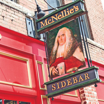 Serving as a point of interest, McNellie's sidebar sign featured in this print gives visitors a reference to where they can directly access the quietest bar in this 3-tiered building.