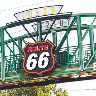 A Route 66 sign on the pedestrian bridge on 11st Street at Cyrus Avery Plaza in Tulsa Oklahoma. A tribute and memorial to this historic piece of Americana.