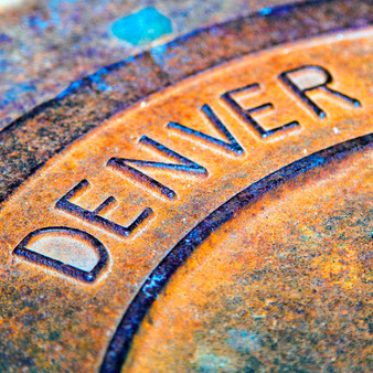 This image highlights the word Denver on a distressed city manhole cover.