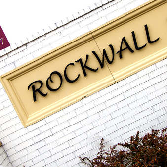 "The city of Rockwall has, sitting beneath it, a row of hard mineral stones which appear to be stacked, long and narrow, forming what gives the impression of a ""rock wall."""