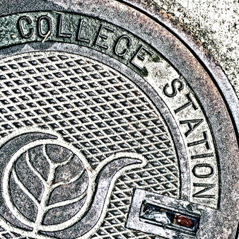 The College Station manhole is distinct as it depicts a horsehoe wrapping around a tree of life. Similarly, at College Station's biggest university known across the country - Texas A &M - a road shaped as a horsehoe surrounds the campus.