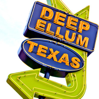 This sign is located in the lively historic Deep Ellum entertainment district,  located near downtown Dallas. Deep Ellum is a thriving artist community known for its vibrant street murals, quirky shops, art galleries, concert venues and restaurants. Visit Deep Ellum at night to see this sign come alive!
