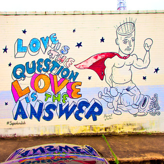 """The mural features a superhero, with the phrase """"Love is the question, Love is the answer,"""" and was produced in conjunction with the Austin-based advertising firm GSD&M. The superhero-themed artwork is part of a campaign to raise money for Superhero Kids, an organization that provides financial support for families of kids at Dell Children's Blood and Cancer Center."""