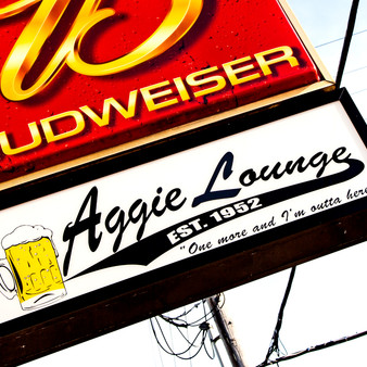 "<p>The Aggie Lounge, better known to locals and regulars as ""The Lou"" is the closest thing you'll find in Manhattan to a dive bar. This place opened in 1952 and has been rockin' ever since.<p><p>Click &lsquo;Choose a Product&rsquo; above to get this image hand printed on a ceramic 4x4 custom coaster, cutting board, magnet, ceramic trivet, ornament, dog tag or canvas.</p>"