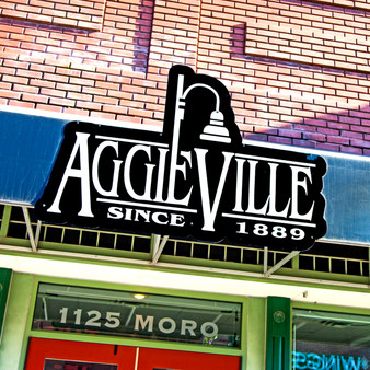 <p>Aggieville is the oldest Entertainment and Shopping District in KS. It is home to almost 100 Restaurants, Shops, Bars, and Entertainment Venues.<p><p>Click &lsquo;Choose a Product&rsquo; above to get this image hand printed on a ceramic 4x4 custom coaster, cutting board, magnet, ceramic trivet, ornament, dog tag or canvas.</p>