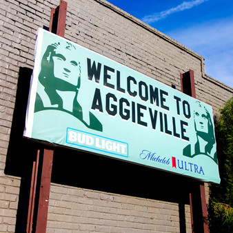 <p>Aggieville is the oldest entertainment and shopping district in KS and it's home to almost 100 restaurants, shops, bars, and entertainment venues.<p><p>Click &lsquo;Choose a Product&rsquo; above to get this image hand printed on a ceramic 4x4 custom coaster, cutting board, magnet, ceramic trivet, ornament, dog tag or canvas.</p>
