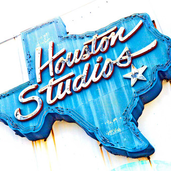 Acting as a reference point to those searching for the Houston Studios is this pronounced blue sign featuring a whimsical, cursive font.