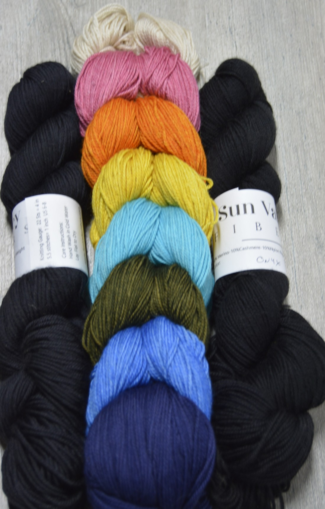 Painted Bricks Jewel Tones contains 8  100 yard skeins of the following colors:  Whisper, Persuasion, Tequila Sunrise, Coreopsis, Refreshing, Sherwood Forest, Cornflower, Ambassador And 2  400 yard skeins of Onyx.