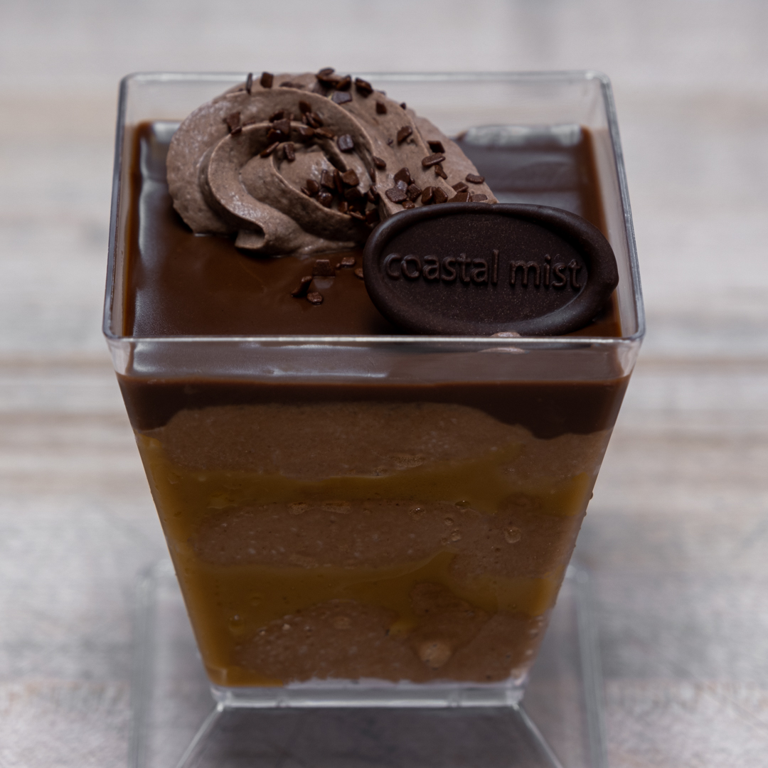Layers of dark chocolate mousse and Vanilla Salt Caramel are topped with dark chocolate glaze and dark chocolate whipped cream.