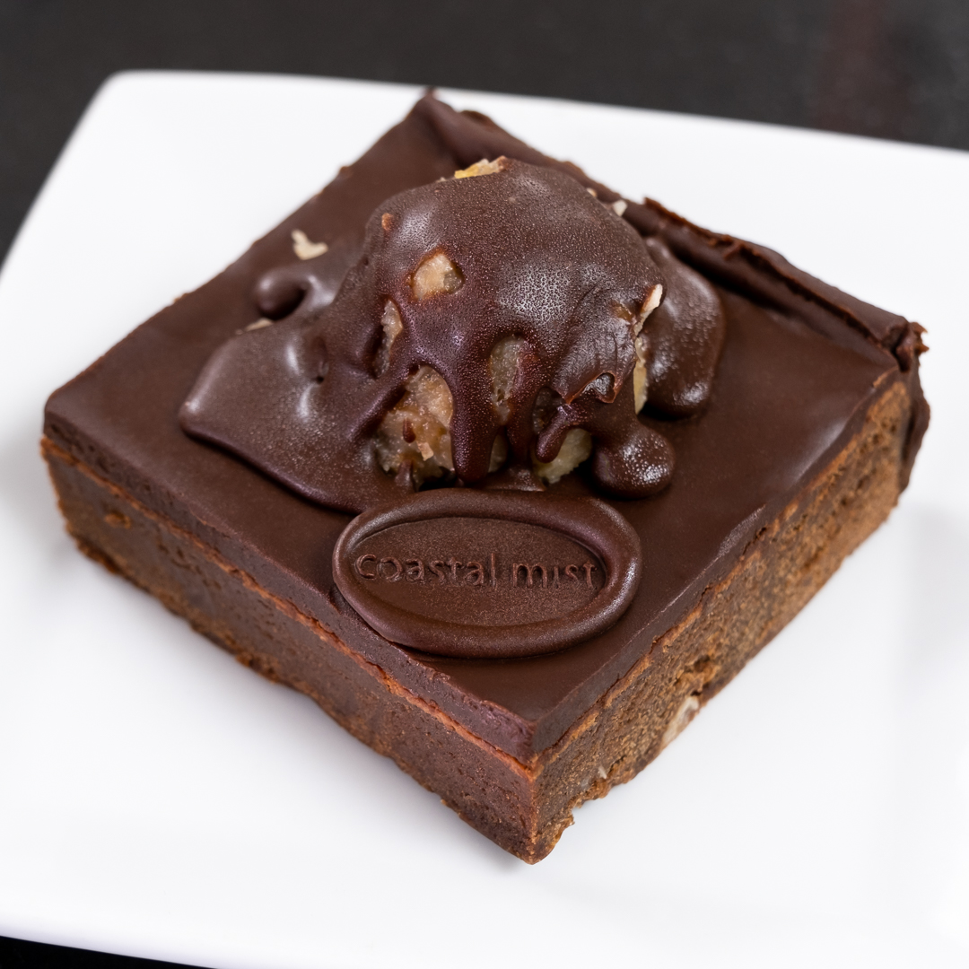 Our moist dark chocolate Brownie is mixed with a German chocolate filling and topped with coconut & walnuts.