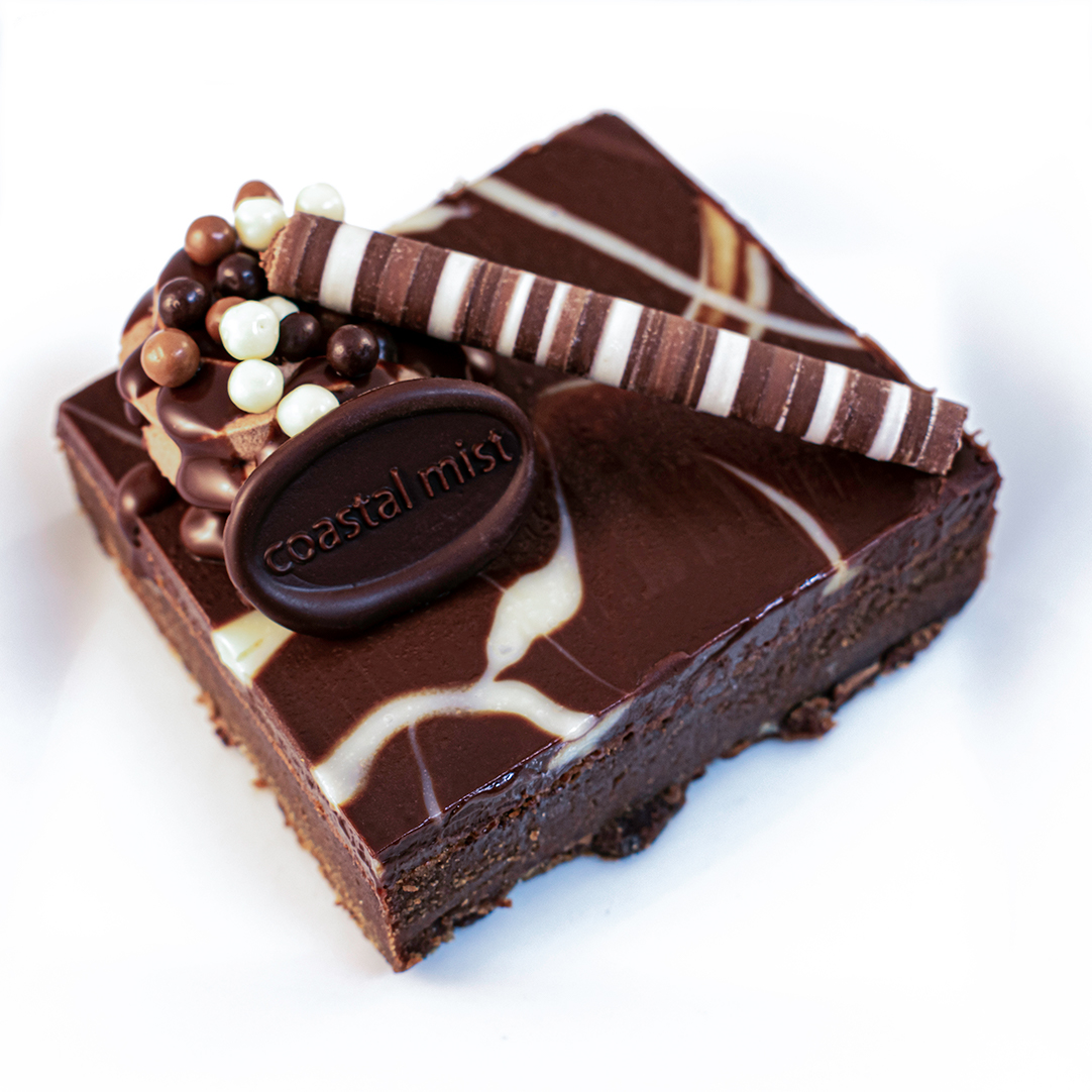 Our dark decadent brownie is mixed with bits of Dark, Milk, and White Belgian Chocolate. It is then topped with Dark, Milk, and White Chocolate glazes.