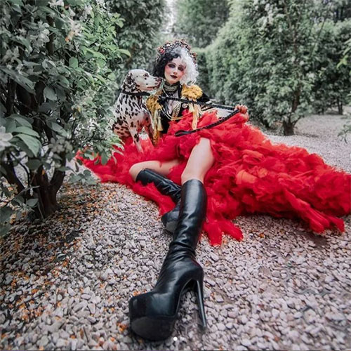 Cruella cosplay in red dress with dalmatian in forest