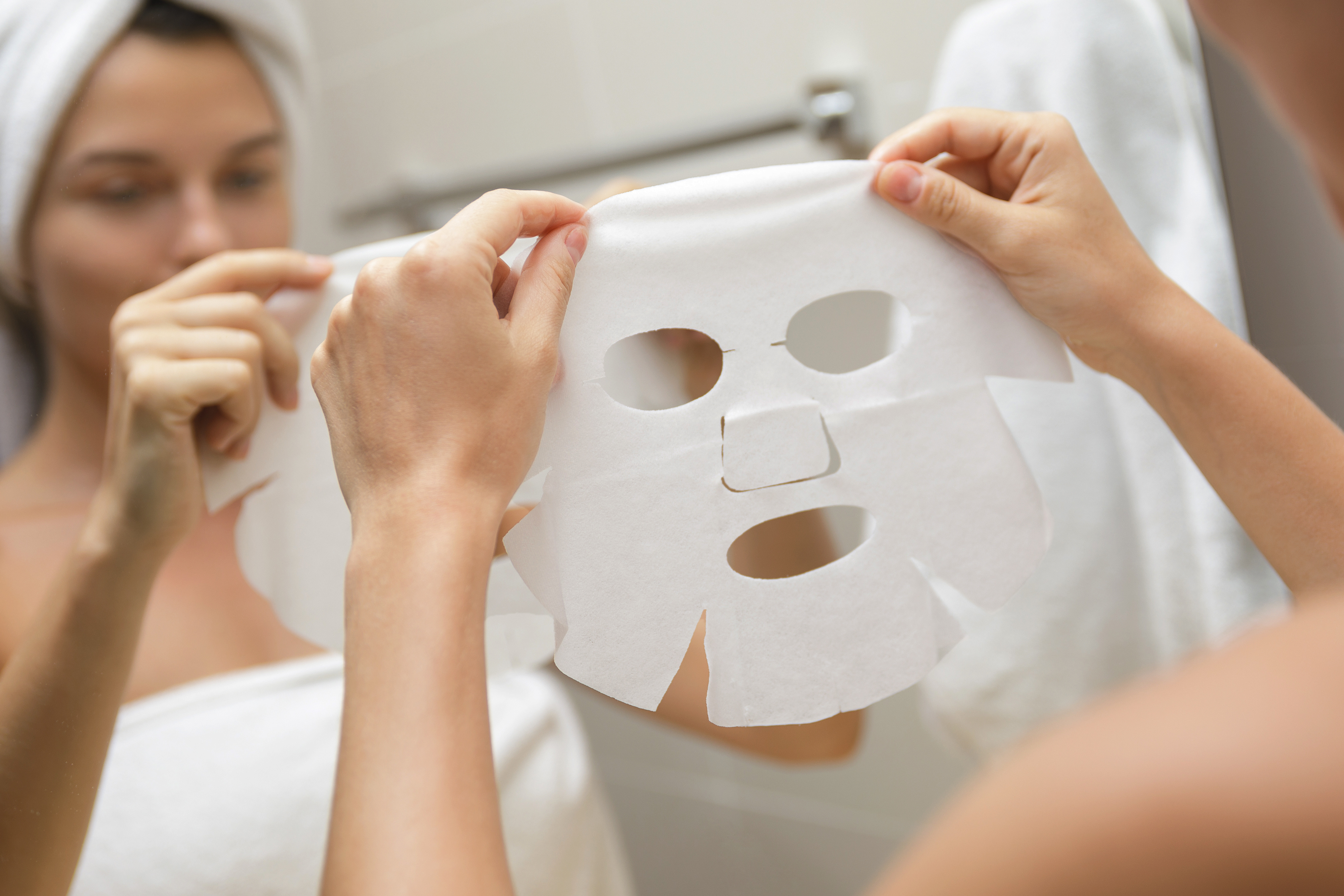 Korean skincare Spa at home. Woman in bathroom is applying facial sheet mask
